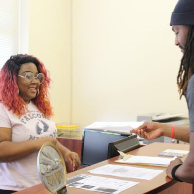 Registrar official assisting a student