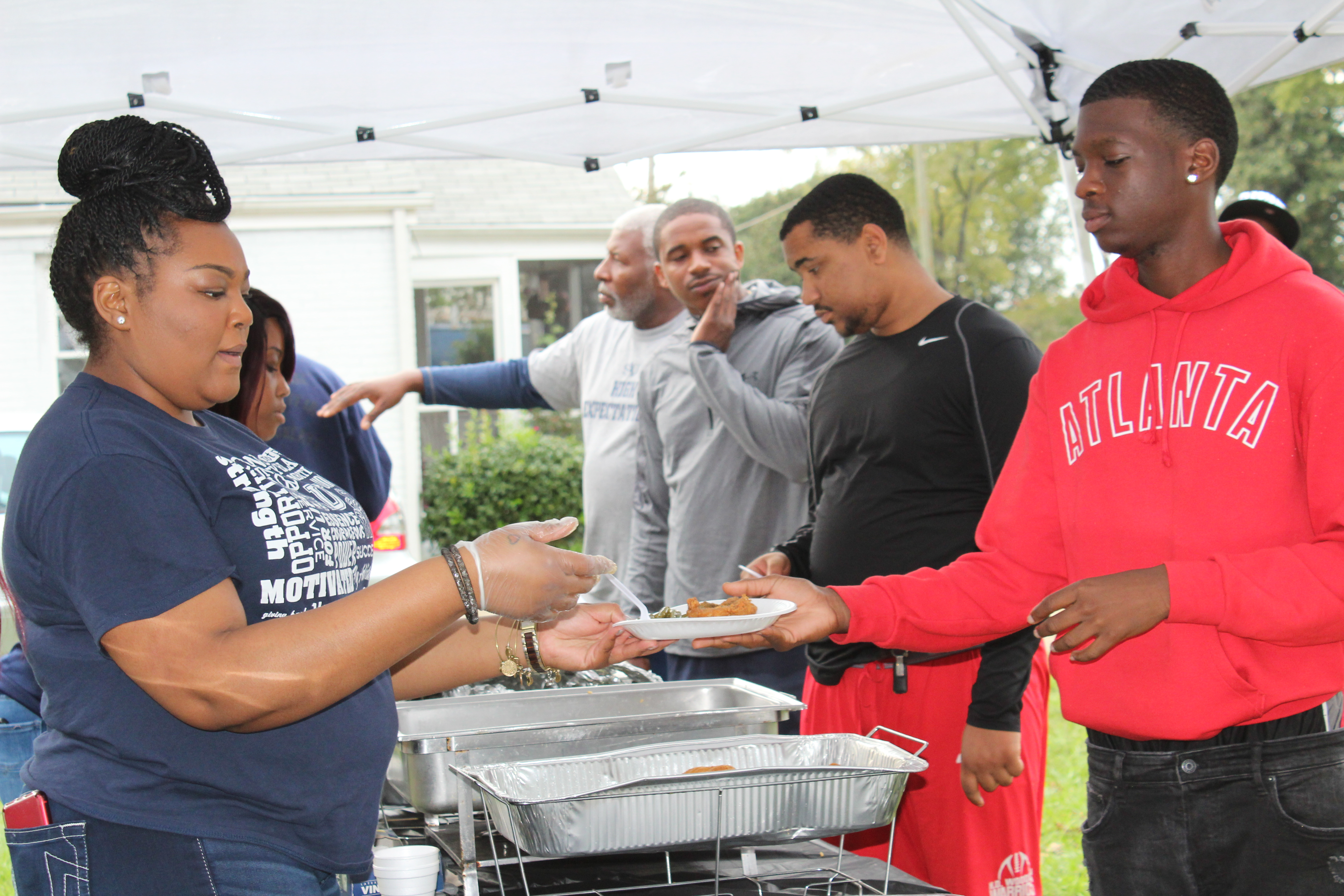 Line of students getting plates of fish from alumni